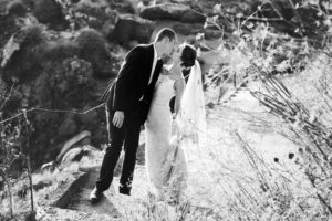 Happy bride and groom kissing and walking on stairs in mountains
