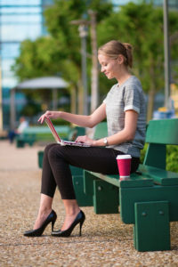 10 tips how to save money in Paris. Young beautiful business woman drinking coffee and working on her laptop outdoors