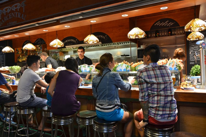 Gimme Gastronomy Tour. Spain (10 Days). Barcelona - August 21: customers seated at a tapas bar at La Boqueria market in Barcelona, Spain on Augut 21, 2014. The market is one of the oldest in Europe and a popular tourist attraction.