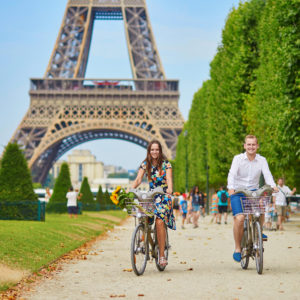 10 tips how to save money in Paris. Romantic couple riding bicycles near the Eiffel tower in Paris