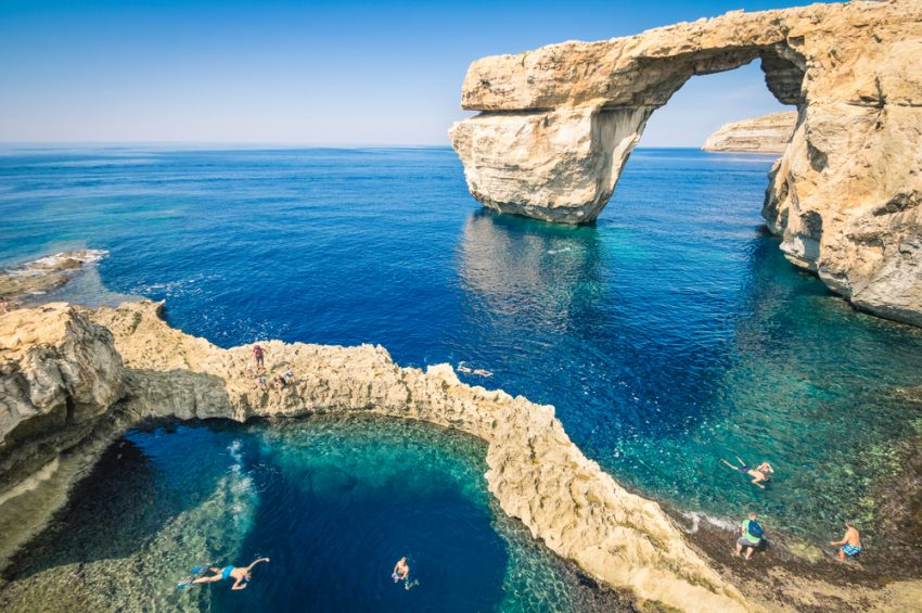 How To Travel Sustainably. The world famous Azure Window in Gozo island - Mediterranean nature wonder in the beautiful Malta - Unrecognizable touristic scuba divers