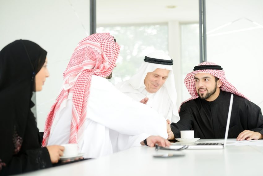 Etiquette in the United Arab Emirates. Successful Arabic business people shaking hands over a deal