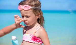 How to Avoid Getting Sick on a Cruise. Young mother applying sunblock cream on her daughter's nose