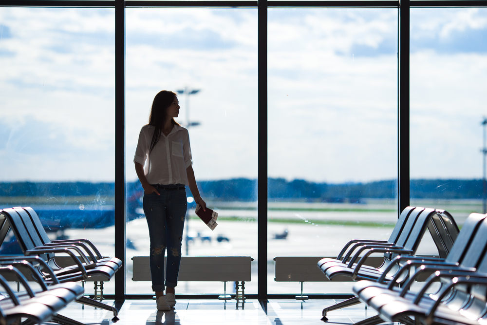 Silhouette of passenger in an airport lounge waiting for flight aircraft. Photo: depositphotos.com
