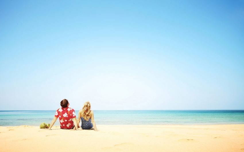 The World's Most Relaxing Vacation Spots. Young happy couple sitting on yellow sand by blue sea