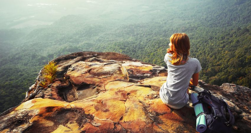 Travel as a Personal Development Tool. Young woman sitting on a rock with backpack and looking to the horizon