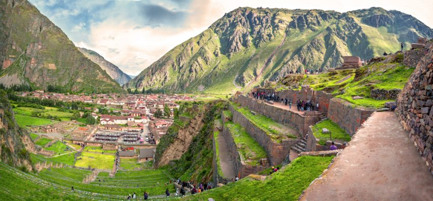 Why Peru Should Be your Next Travel Destination. Ollantaytambo, old Inca fortress in the Sacred Valley in the Andes mountains of Cusco, Peru, South America. Panorama of Machu Pichu with Huayna Picchu, rainforest jungle and mountains with blue sky in the background.