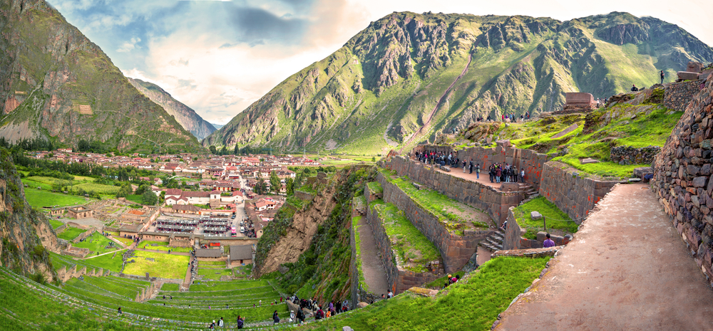 Ollantaytambo, old Inca fortress in the Sacred Valley in the Andes mountains of Cusco, Peru, South America. Panorama of Machu Pichu with Huayna Picchu, rainforest jungle and mountains with blue sky in the background. Photo: depositphotos.com