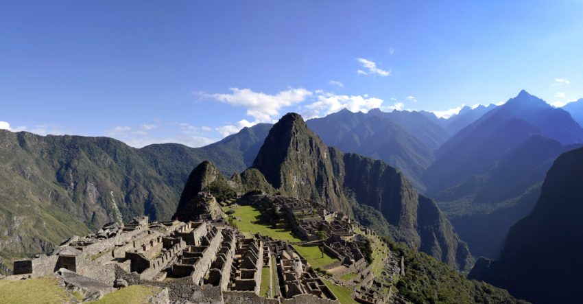 Why Peru Should Be your Next Travel Destination. Panorama of Machu Pichu with Huayna Picchu, rainforest jungle and mountains with blue sky in the background.