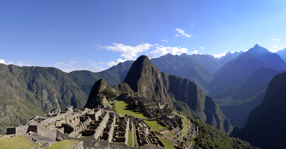 Panorama of Machu Pichu with Huayna Picchu, rainforest jungle and mountains with blue sky in the background. Photo: depositphotos.com
