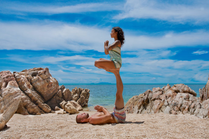 BEST HONEYMOON ACTIVITIES. Beautiful couple doing acro yoga on the beach