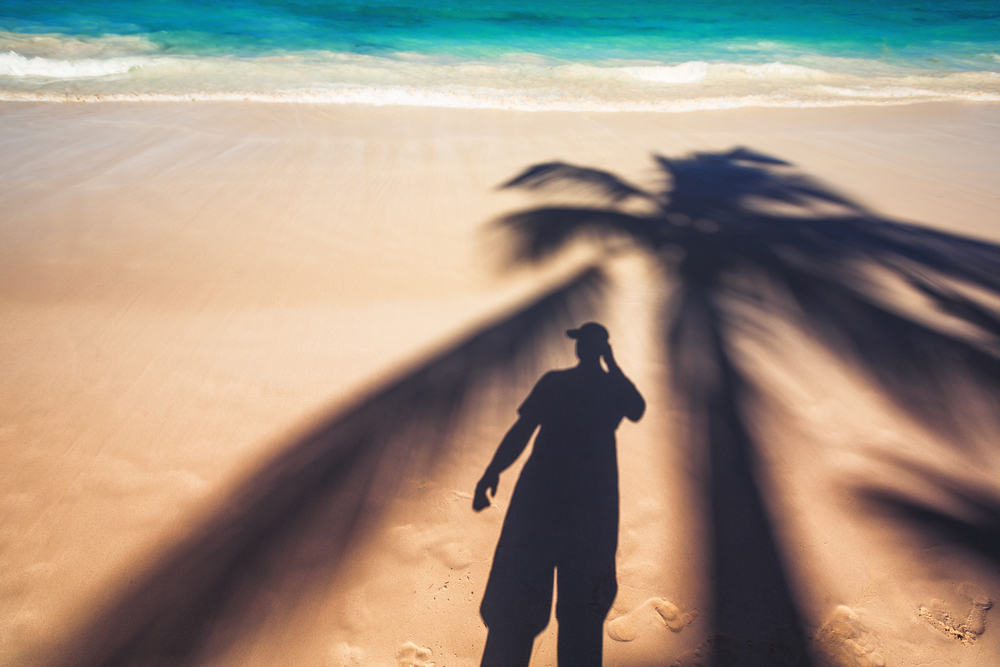 Man and palm tree shadows on tropical exotic beach