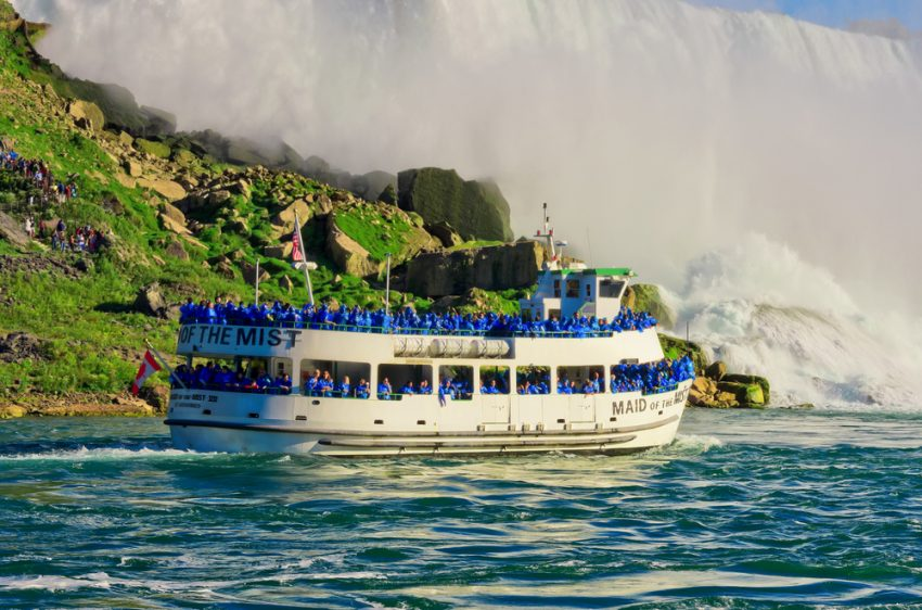 Five Things to Do in Niagara Falls. Niagara Falls, USA - September 24, 2016: Ferry Maid of the Mist in the Niagara River against American waterfall. Niagara Falls.