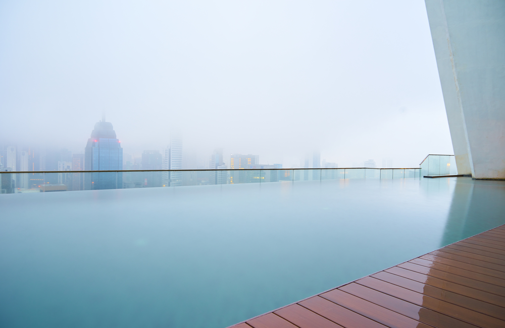 Swimming pool on roof top with beautiful city skyline view,early morning with mist ,  kuala lumpur malaysia.