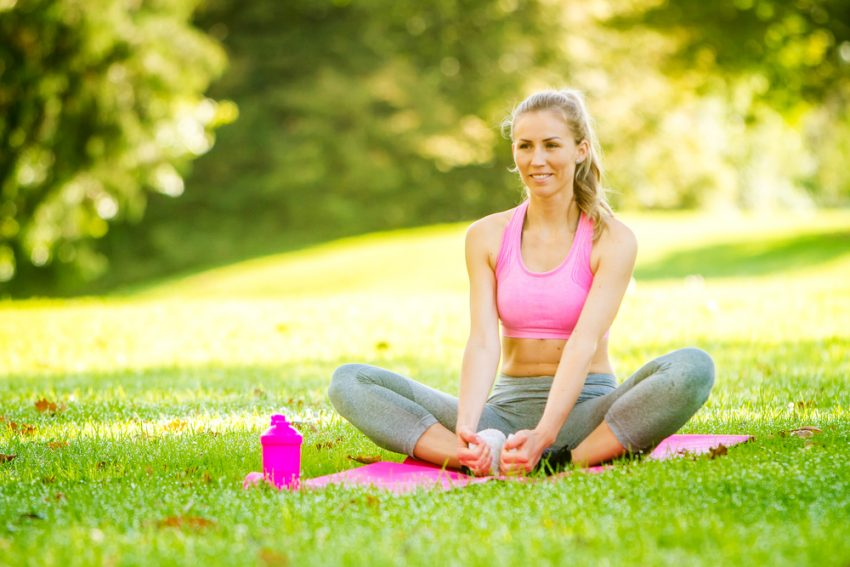 Fitness Tourism. young happy smiling caucasian woman doing exercises in the park, outdoor fitness