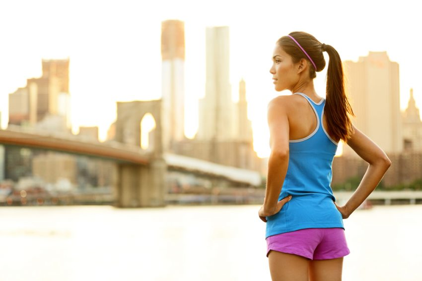 Fitness Tourism. Fitness woman runner relaxing after city running and working out outdoors in New York City, USA. Girl looking and enjoying view of Brooklyn Bridge. Mixed race Asian Caucasian female model.