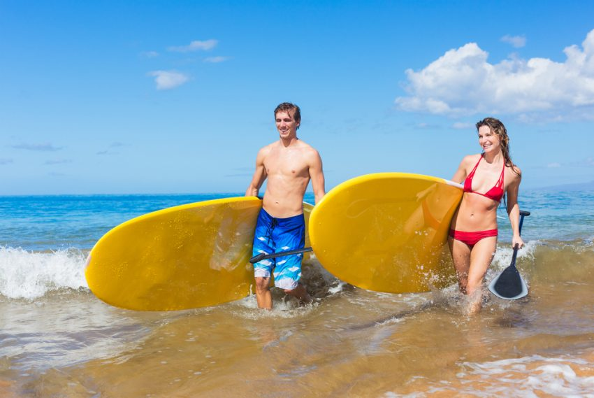 Fitness Tourism. Attractive Couple with Stand Up Paddle Boards, SUP, on the beach in Hawaii