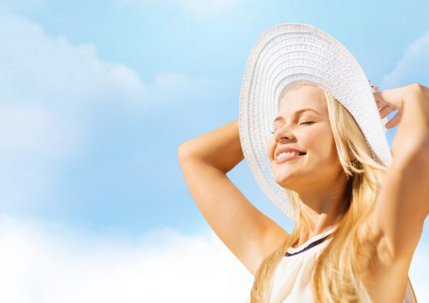 How to Stay Healthy During your Summer Trip 2017. fashion and lifestyle concept - beautiful woman in hat enjoying summer outdoors