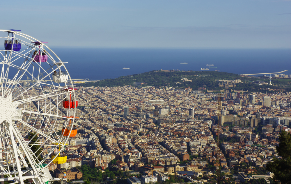 Meet Your Kids' Favorite Characters at the World's Best Amusement Parks. Barcelona, Spain - 2014, April 27: People on a huge ferris wheel with panoramic view over Barcelona. On April 2014 in Barcelona, Spain.