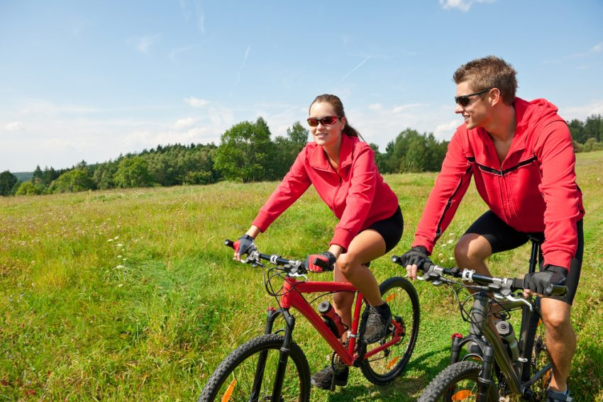 How to Stay Healthy During your Summer Trip 2017. Young couple riding mountain bike in spring meadow nature on sunny day