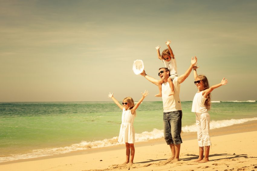 How to Stay Healthy During your Summer Trip 2017. Happy family walking at the beach at the day time. Concept of friendly family.