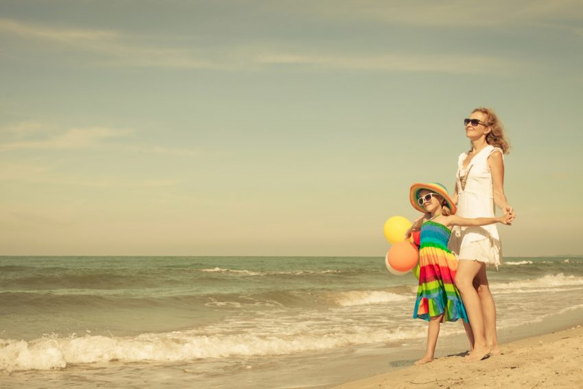 How to Stay Healthy During your Summer Trip 2017. Mother and daughter playing with balloons on the beach at the day time. Concept of friendly family.
