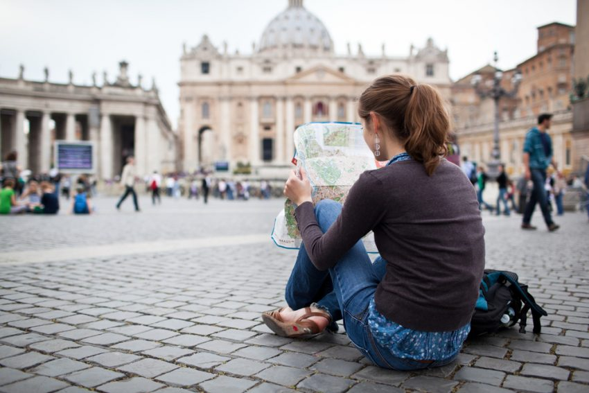 Reasons to Use A Travel Advisor in 2017. Pretty young female tourist studying a map at St. Peter's square in the Vatican City in Rome