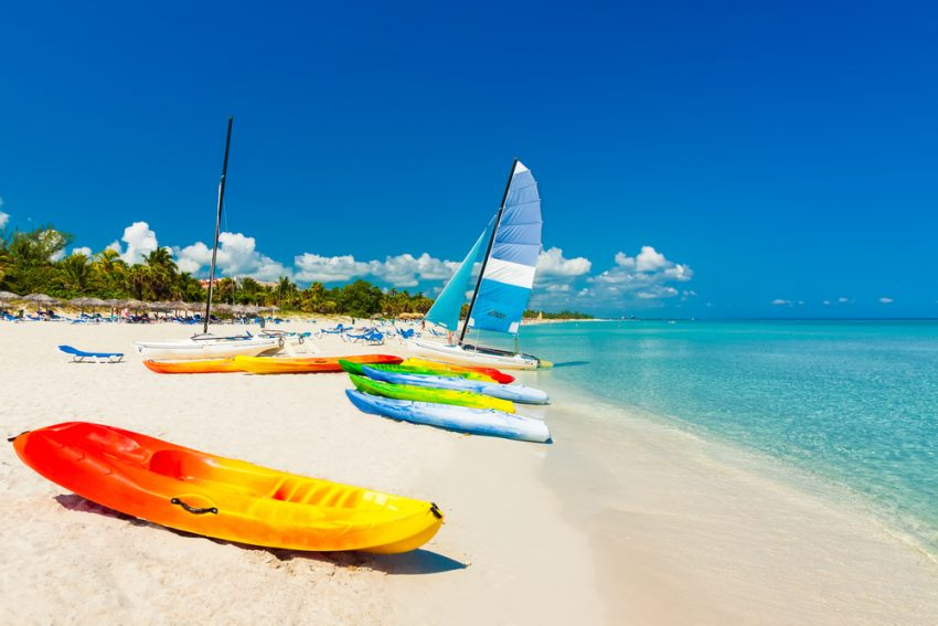 Why Cuba is One of the Top Caribbean Destinations. Colorful kayaks and sailing boats on a tropical beach in Cuba