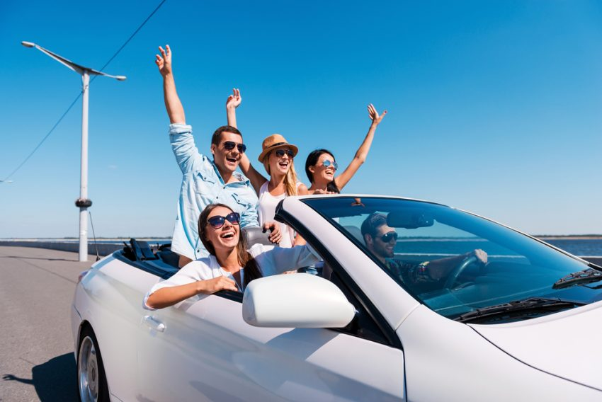 Tips for Travel Addicts. Nothing but friends and road ahead. Group of young happy people enjoying road trip in their white convertible and raising their arms up
