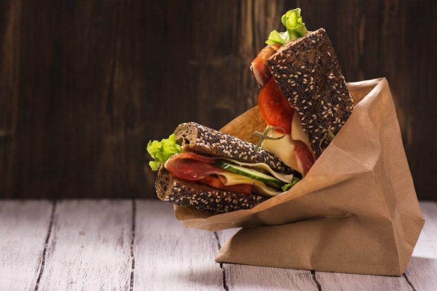 Favorite Ideas For Healthy Eating On The Road. Rye bread sandwiches with ham, cheese and vegetables in a craft paper bag. Take away food. Selective focus