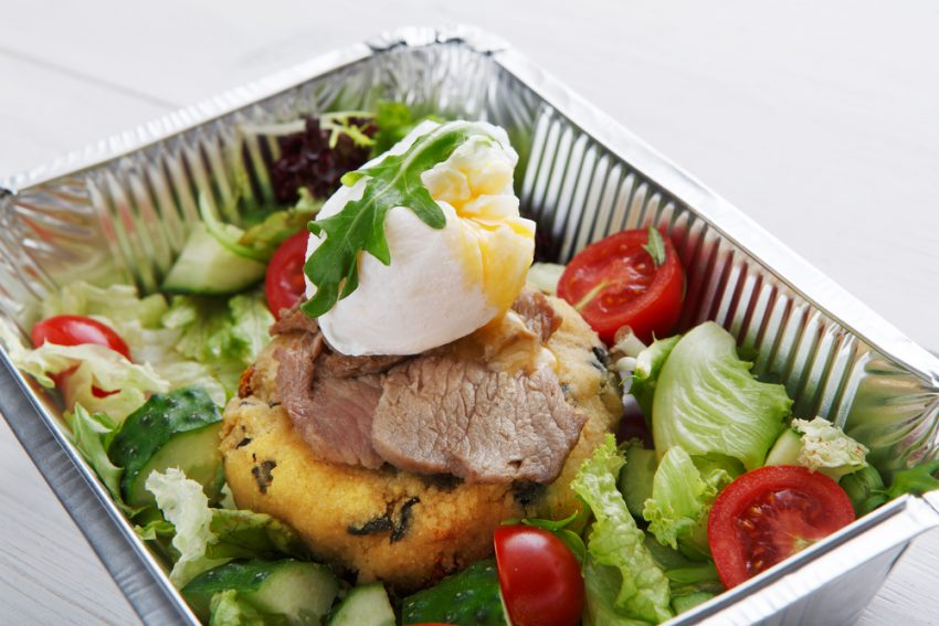 Favorite Ideas For Healthy Eating On The Road. Restaurant food delivery in foil box. Poached egg with runny yolk closeup on veil steak medium rare with fresh vegetable salad and couscous cushion. Dish take away closeup, healthy meal.