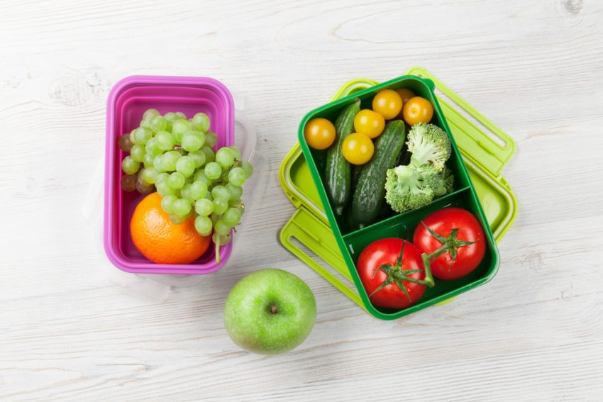 Favorite Ideas For Healthy Eating On The Road. Lunch box with vegetable and fruits on wooden table. Kids take away food box. Top view