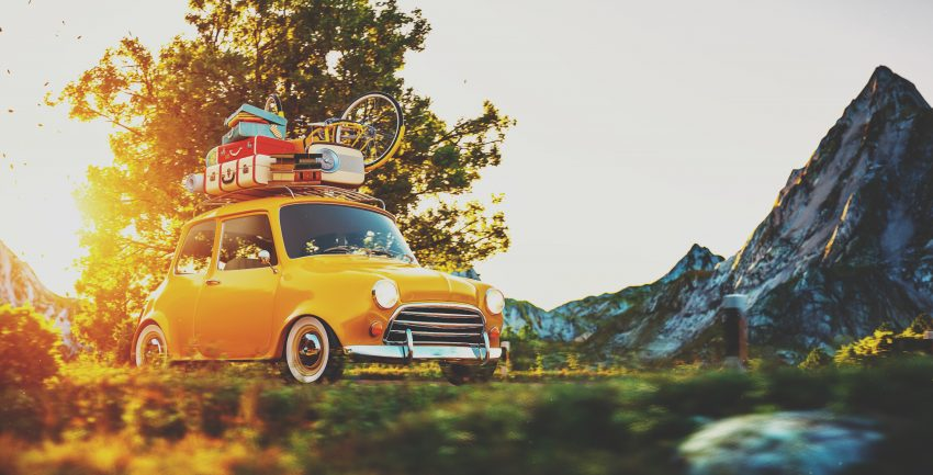Tips for Ideal Road Trip. Cute little retro car with suitcases and bicycle on top goes by wonderful countryside road at sunset
