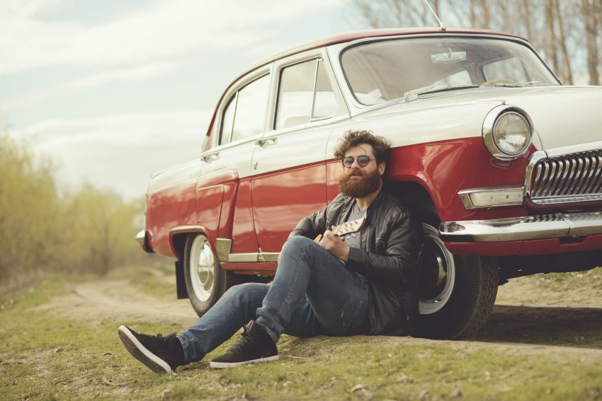 Tips for Ideal Road Trip. Bearded man playing guitar outdoors near retro car