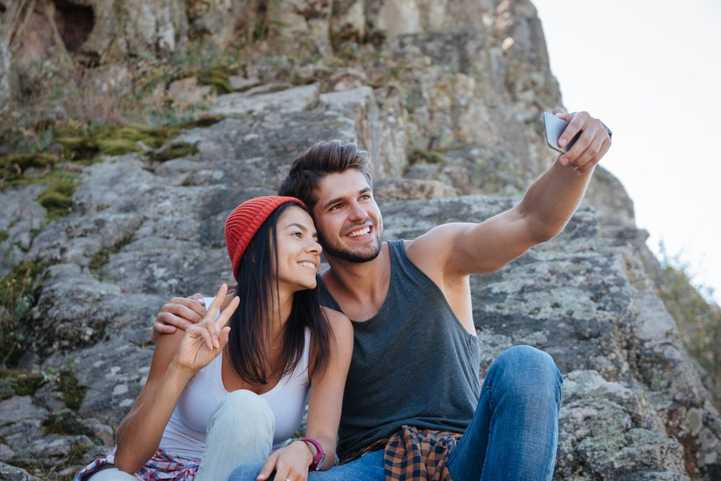 Couple make selfie and sitting on rock