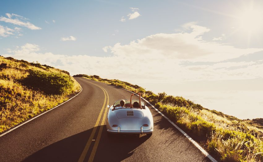 Tips for Ideal Road Trip. Happy Couple Driving on Country Road in Classic Vintage Sports Car