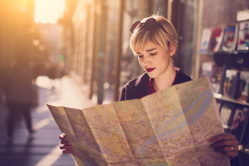 Ten Reasons to Use a Travel Agent. Young beautiful female traveler standing on the street and looking at the map