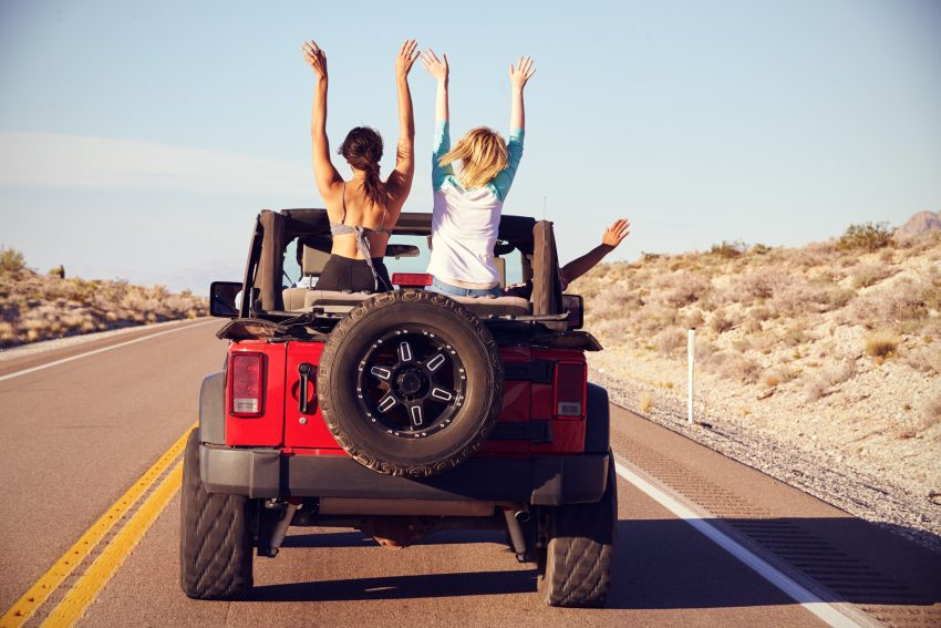 Tips for Ideal Road Trip. Rear View Of Friends On Road Trip Driving In Convertible Car