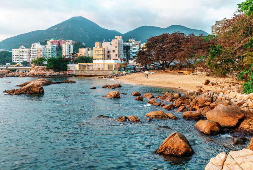 Top Places to Enjoy in Hong Kong. Rocky sea shore and small sandy beach of Stanley Bay in Hong Kong. Beautiful scenic landscape with water, mountains, rocks and buildings